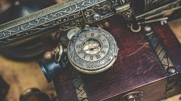 Pingente de relógio de bronze do vintage e pistola gravada Foto Premium