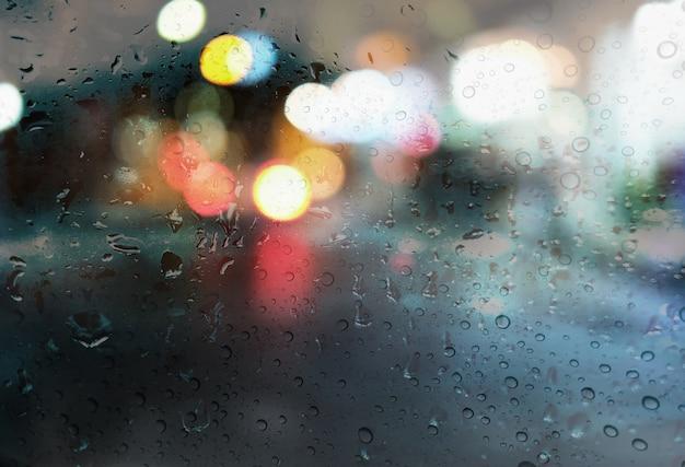 Pingos de chuva com luz bokeh no fundo de estação de chuva de estrada Foto Premium