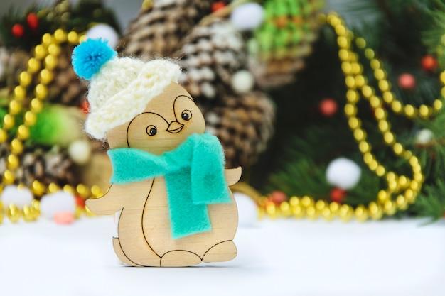 Pinguim de brinquedo de natal de madeira com um chapéu em um fundo temático Foto Premium