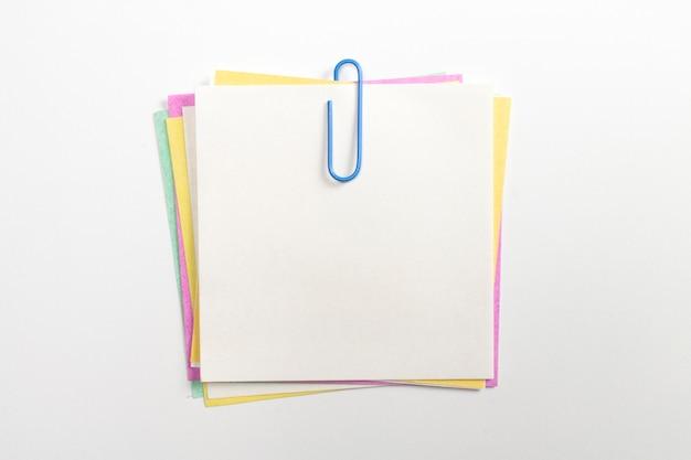 Pino colorido do papel de nota com clipes de papel azuis e isolado no branco. Foto gratuita