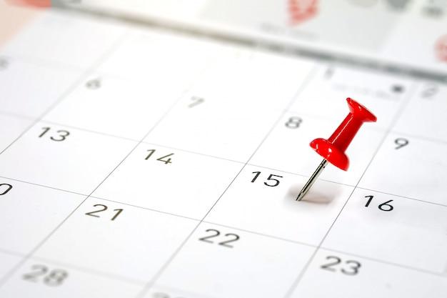 Pinos vermelhos bordados em um calendário no dia 15 com foco seletivo Foto Premium