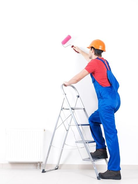 Pintor artesão em pé na escada com rolo, retrato completo em branco Foto gratuita