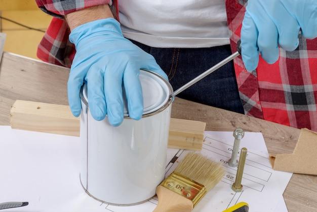 Pintor de casa abre uma lata de tinta com uma chave de fenda Foto Premium