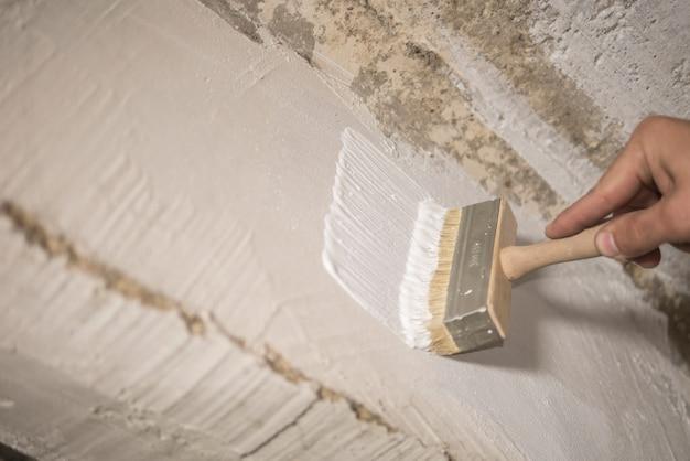 Pintor de casa pinta a parede com tinta branca Foto Premium