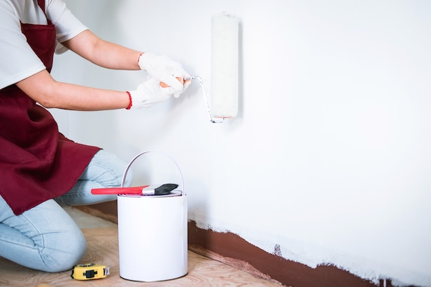 Pintor mão na parede de pintura de luva branca com rolo de pintura na sala, forma e estrutura Foto Premium
