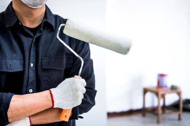 Pintor masculino com braço cruzado segurando o rolo de pintura Foto Premium