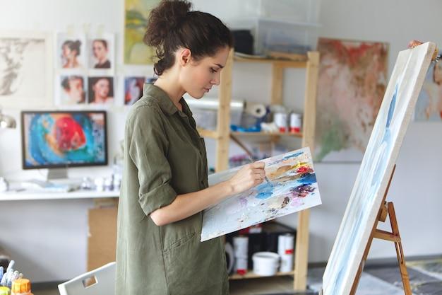 Pintora em seu estúdio de arte Foto gratuita