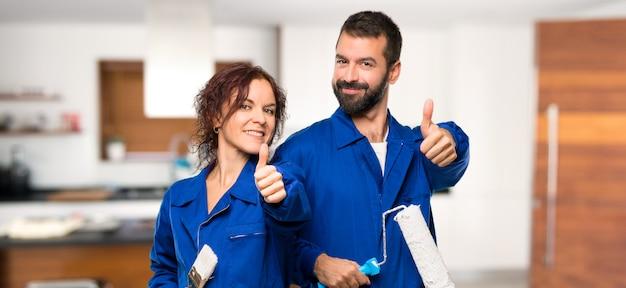 Pintores dando um polegar para cima gesto e sorrindo em casa Foto Premium