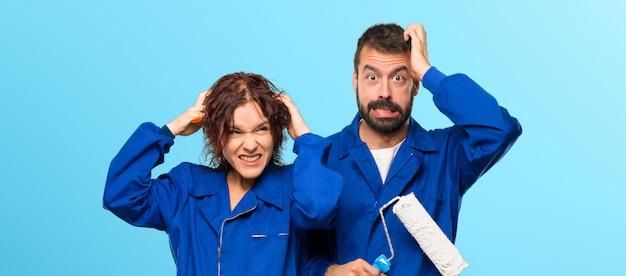 Pintores toma as mãos na cabeça porque tem enxaqueca em fundo colorido Foto Premium