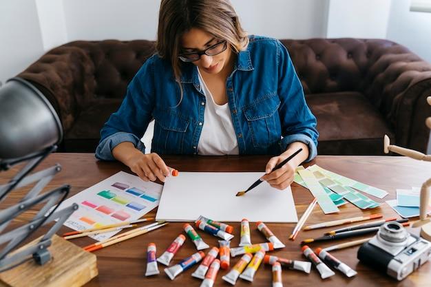 Pintura criativa do artista feminino na mesa Foto gratuita