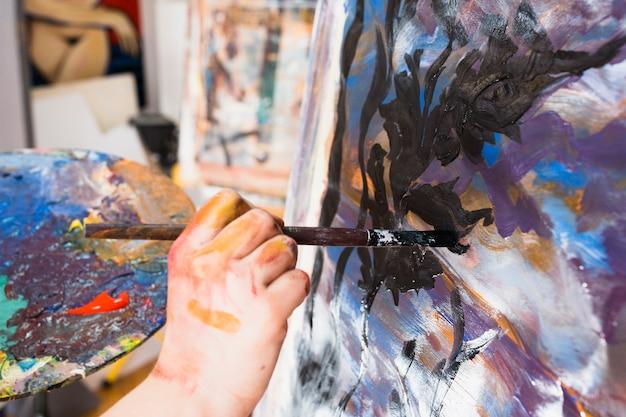 Pintura da mão do artista com pincelada preta na lona Foto gratuita
