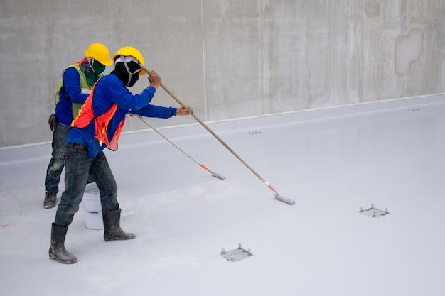 Pintura epoxy do trabalhador da construção no assoalho para a proteção da prova da água Foto Premium