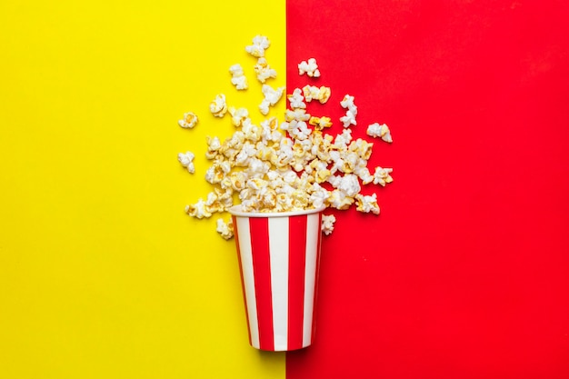 Pipoca em uma caixa de papelão vermelha e branca em um vermelho e amarelo Foto Premium