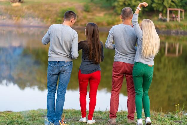 Piquenique com os amigos no lago perto da fogueira Foto Premium