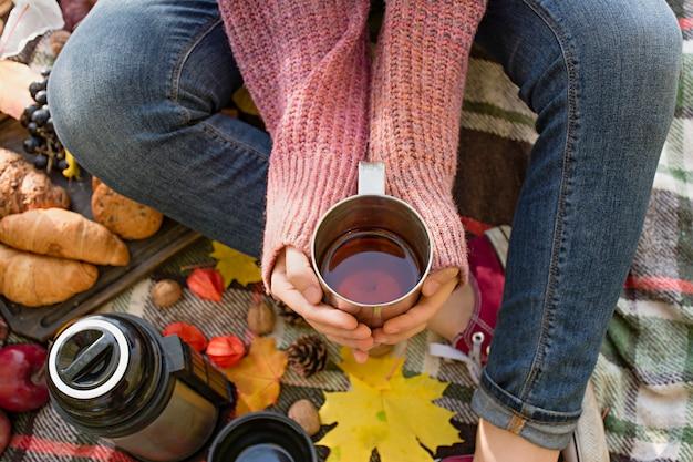 Piquenique de outono no parque, dia quente de outono. a menina tem uma xícara com chá nas mãos dela. cesta com flores em um cobertor no outono amarelo folhas. conceito de outono. Foto Premium