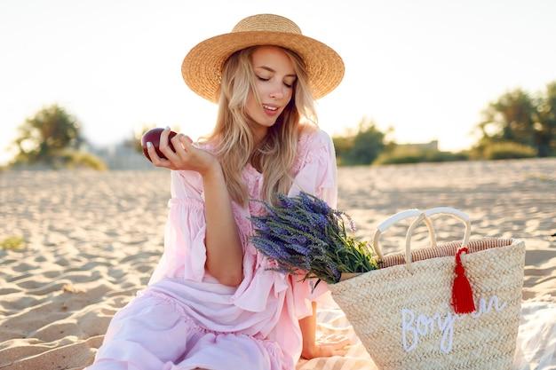 Piquenique na zona rural perto do oceano. mulher jovem graciosa com cabelos loiros ondulados no elegante vestido rosa, curtindo as férias e comendo frutas. Foto gratuita