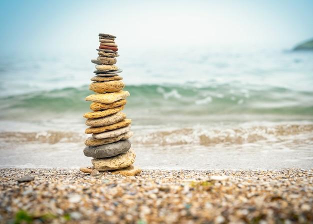 Pirâmide de pedras na areia, simbolizando o zen, harmonia, equilíbrio. energia positiva. oceano ao fundo Foto Premium