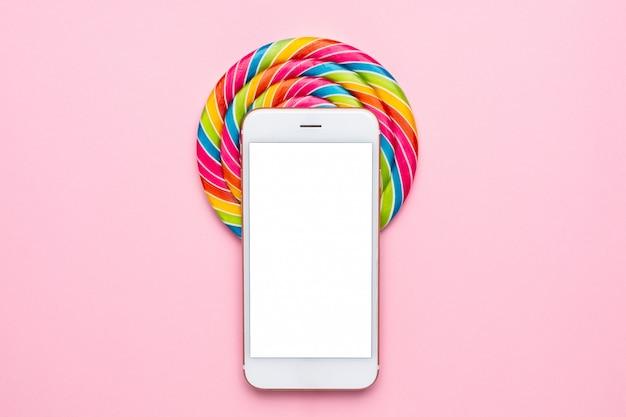 Pirulito colorido e telefone móvel em rosa Foto Premium