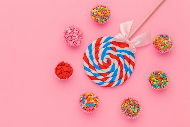 Pirulito e açúcar granulado em taças de papel no fundo rosa, vista superior Foto Premium