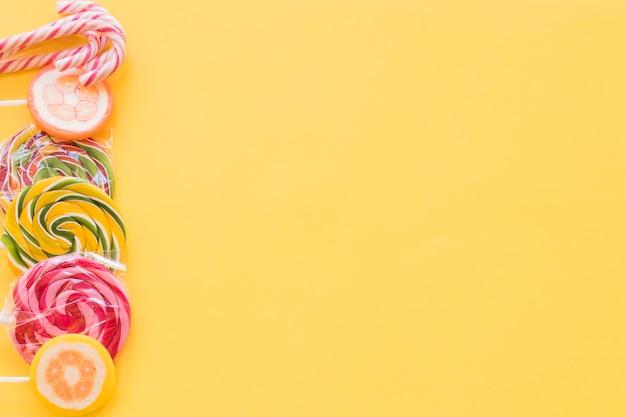 Pirulitos coloridos e doces de bengala de natal em pano de fundo amarelo Foto gratuita