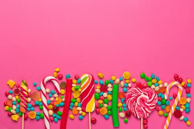 Pirulitos coloridos em um fundo rosa Foto Premium
