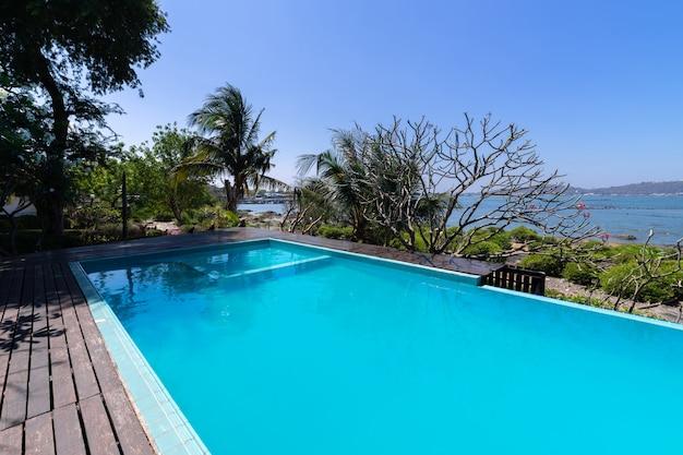 Piscina água azul e jardim tropical com vista para o mar fundo Foto gratuita