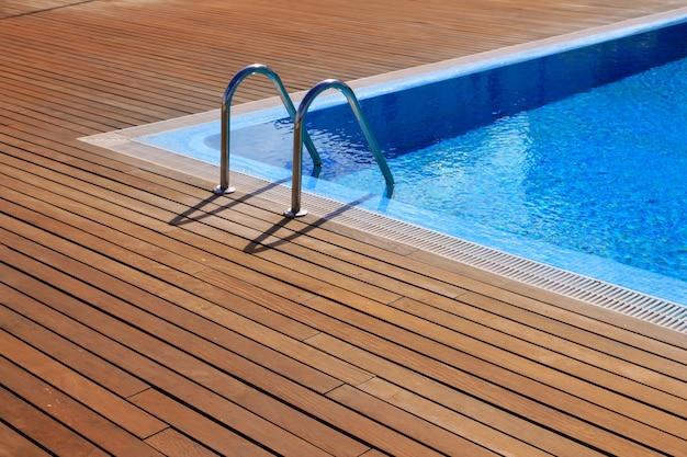Piscina azul com piso de madeira teca Foto Premium