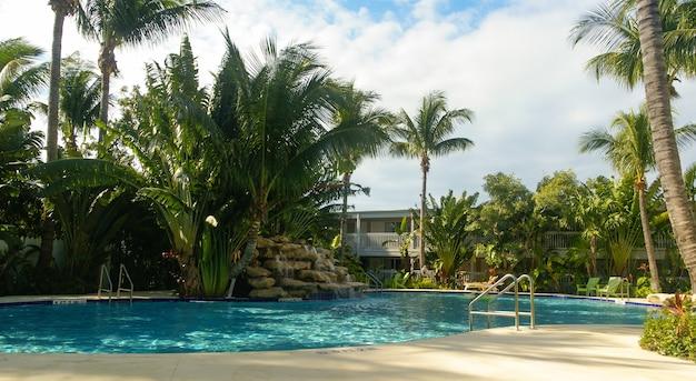 Piscina cercada por palmeiras perto de um hotel Foto gratuita