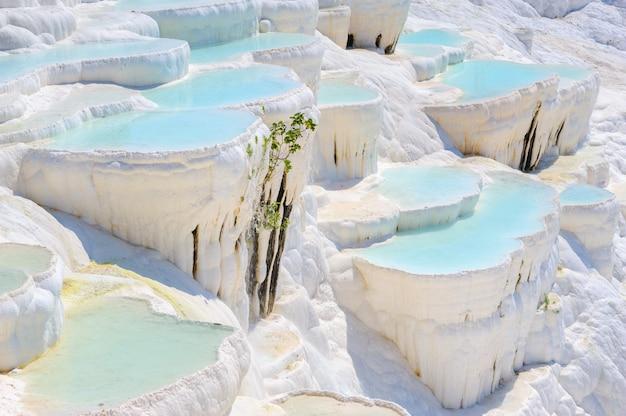 Piscinas ciano azul do travertino da água em hierapolis antigo, agora pamukkale, turquia Foto Premium