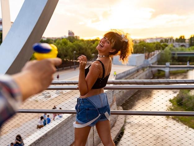 Pistolas de água pessoas brincando e se divertindo em um dia quente de verão. Foto Premium