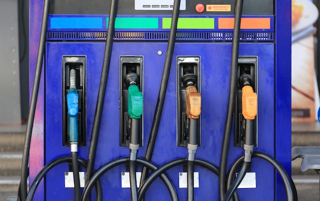 Pistolas de combustível multi cor na estação de combustível. Foto Premium