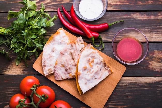 Pita deliciosa na tábua de cortar perto de molhos entre vegetais e ervas Foto gratuita