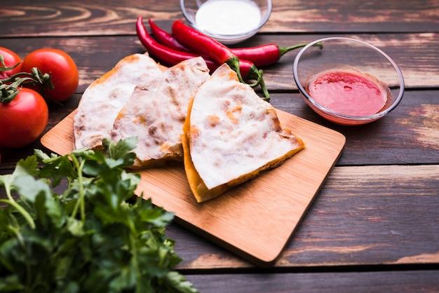 Pita deliciosa na tábua de cortar perto de molhos entre vegetais Foto gratuita