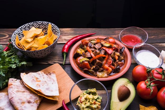 Pita deliciosa perto de refeição entre legumes e nachos Foto gratuita