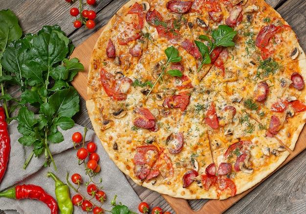 Pizza assada com folhas de linguiça defumada, cogumelos, tomate, queijo e rúcula Foto Premium