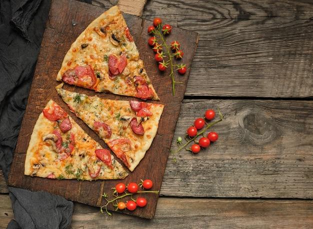 Pizza assada com linguiça defumada, cogumelos, tomate, queijo e endro Foto Premium