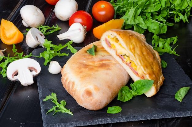 Pizza calzone com molho de tomate, queijo, ervas, cogumelos e salsichas. comida italiana. Foto Premium