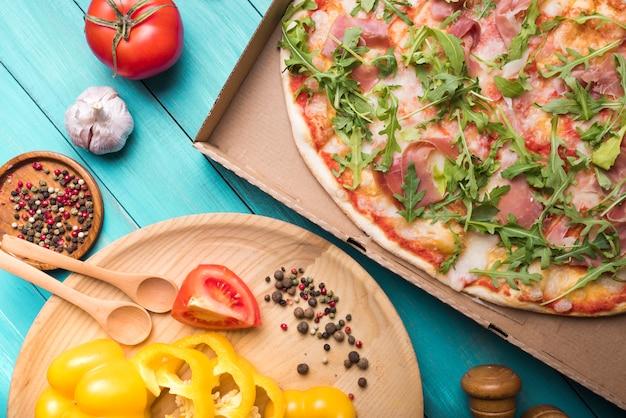 Pizza caseira com pimentão; alho tomate e especiarias na mesa de madeira Foto gratuita