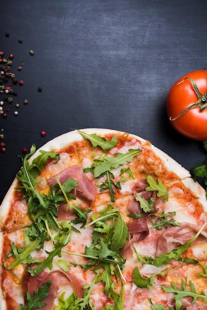 Pizza com cobertura de folhas de bacon e rúcula perto de tomate suculento e pimenta preta na superfície preta texturizada Foto gratuita