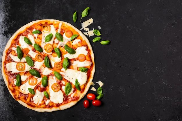 Pizza com espaço de cópia na mesa preta Foto gratuita