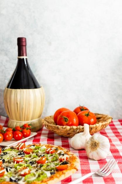 Pizza com garrafa de vinho grande Foto gratuita