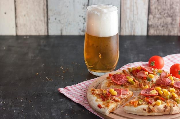 Pizza com milho, salsicha, tomate em uma placa de madeira e cerveja light com espuma em um copo Foto Premium