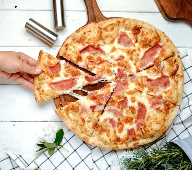 Pizza com presunto na mesa Foto gratuita