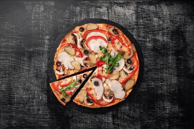 Pizza com queijo, presunto, pepinos em conserva, carne e azeitonas na placa de giz. Foto Premium