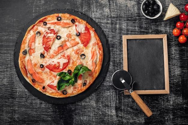 Pizza com queijo, truta, tomates, azeitonas e camarões no quadro de giz. Foto Premium