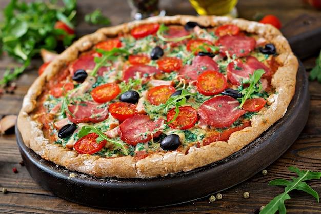 Pizza com salame, tomate, azeitona e queijo em uma massa com farinha de trigo integral. comida italiana. Foto gratuita