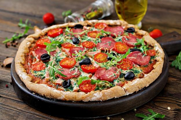 Pizza com salame, tomates, azeitonas e queijo em uma massa de pão com farinha de trigo integral. comida italiana. Foto Premium