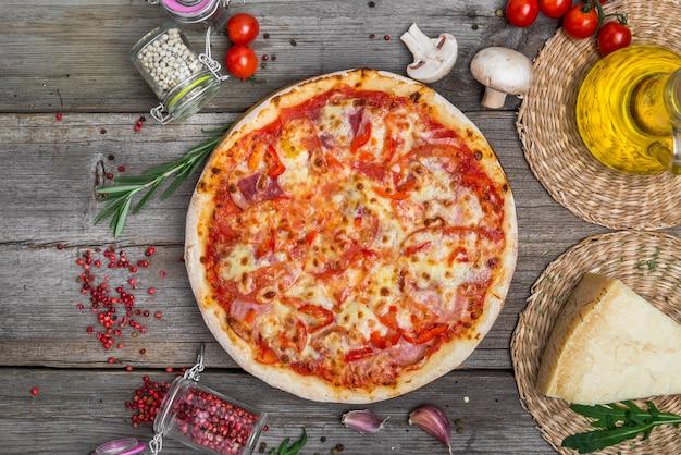 Pizza com tomate, queijo mussarela, azeitonas pretas e manjericão. deliciosa pizza italiana na placa de madeira da pizza. vista de mesa Foto Premium