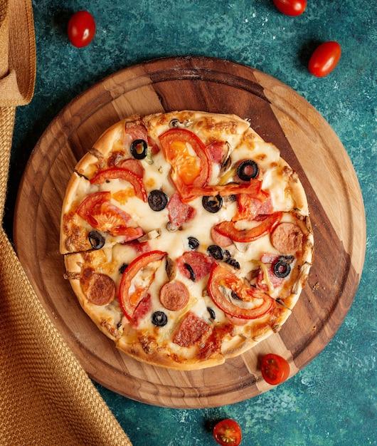 Pizza crocante com tomates, azeitonas e salsichas Foto gratuita