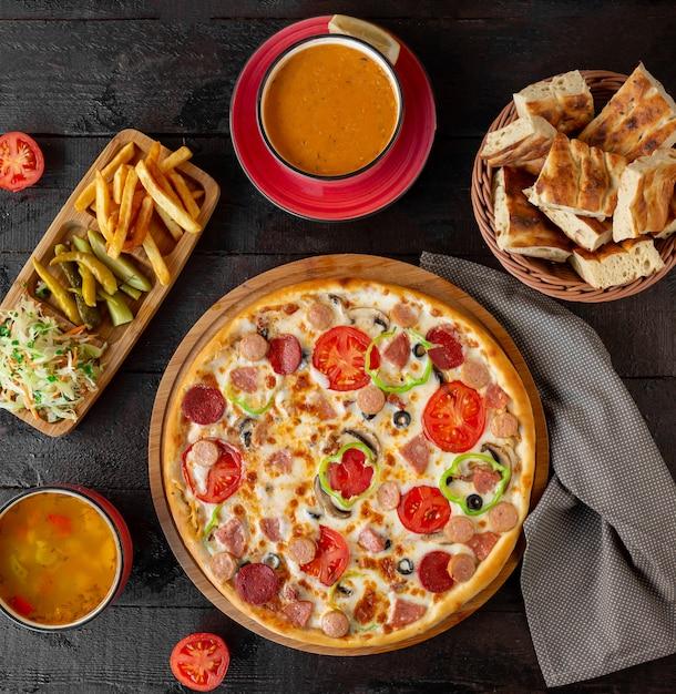 Pizza de calabresa com sopas de lentilha e legumes Foto gratuita